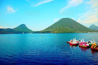 背景の山と水の体中の小型船の写真・画像素材[901146]