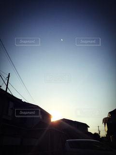 街に沈む夕日と現れた月の写真・画像素材[849336]