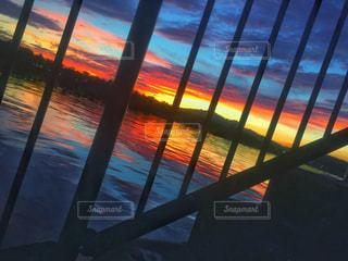 フェンス越しの夕焼けの写真・画像素材[847321]
