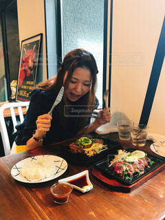 食品のプレートをテーブルに座っている女性の写真・画像素材[1266145]