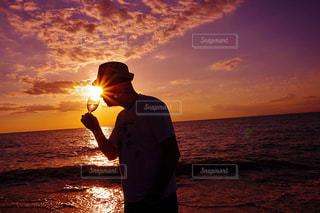バック グラウンドで夕焼けのビーチに立っている人 - No.874159