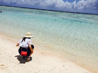 海の横にある砂浜に座っている男の写真・画像素材[852273]