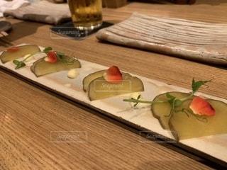 木製のまな板の上に座っている食べ物の皿の写真・画像素材[2350966]