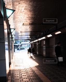 鉄道駅に座っている男の人の写真・画像素材[856610]
