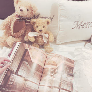 ベッドの上に座っているテディベアの写真・画像素材[2223944]