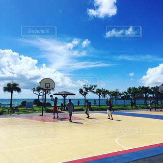 沖縄のビーチの横でバスケットをしている風景の写真・画像素材[856919]