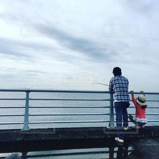 海へ向かって釣りをしている親子の後ろ姿の写真・画像素材[857498]