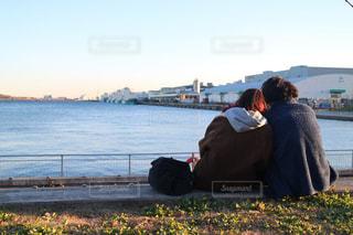 水の体の前にあるベンチに座っている人の写真・画像素材[1025326]
