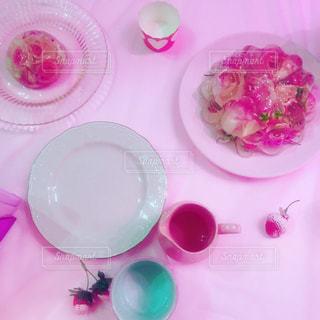 テーブルの上のピンクの花で満ちているプレートの写真・画像素材[1012102]