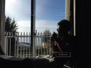 ウィンドウの前に座っている男の写真・画像素材[861327]
