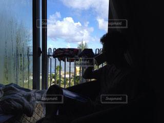 窓の前に座っている男の写真・画像素材[861330]