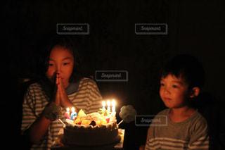 キャンドルとバースデー ケーキの前に立っている少年の写真・画像素材[863660]