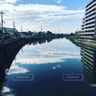 バック グラウンドで市と水の体の上の大きな橋の写真・画像素材[860364]