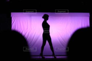 暗い部屋のフラット スクリーンのテレビの前に立っている男の写真・画像素材[864801]