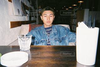 テーブルに座っている男の人の写真・画像素材[860569]