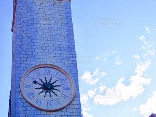 建物の側に時計と大きな背の高い塔の写真・画像素材[872841]
