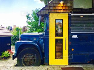 黄色と青のバスは建物の脇に駐車します。 - No.873431