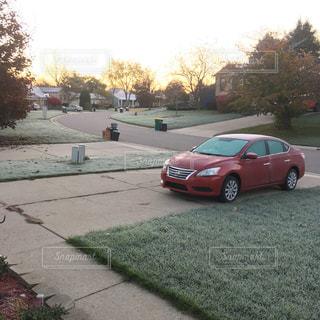 寒い朝の庭 赤い車が停まっている庭の写真・画像素材[860785]