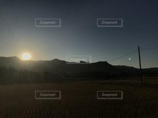 芝生のフィールドに沈む夕日の写真・画像素材[1267449]