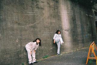 コンクリートの壁の横に立っているペア - No.865804