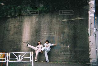 コンクリートの壁の前で踊る2人の写真・画像素材[865805]
