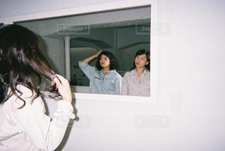カメラにポーズ鏡の前に立っている女性の写真・画像素材[866485]