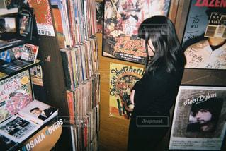 レコードの棚の前に立っている女性の写真・画像素材[868780]