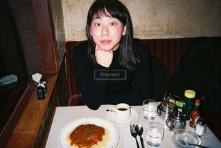 食品のプレートをテーブルに座っている女性の写真・画像素材[868781]