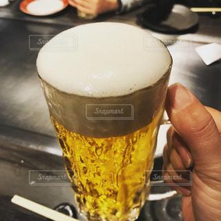 テーブルにビールのグラスを持っている手の写真・画像素材[1035647]