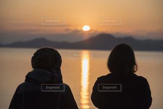 日没の前に立っている人のカップルの写真・画像素材[870291]