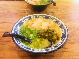 木製テーブルの上の皿の上に食べ物のボウルの写真・画像素材[977818]