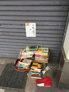 閉店した本屋のシャッター前に積み上げられた古本(2)の写真・画像素材[867337]