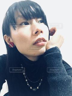 頬杖をつく赤いイヤリングの女性の写真・画像素材[868846]
