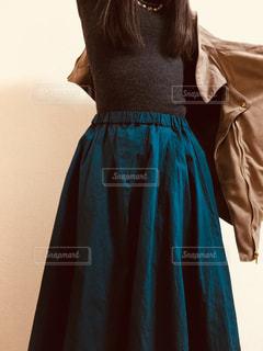 グリーンのロングスカートを履いて上着を羽織ろうとする女性の写真・画像素材[869926]