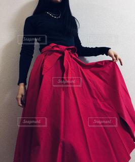 ショッキングピンクのロングスカートの端をつまんで持ち上げる女性の写真・画像素材[869927]