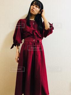 赤いワンピースを着て髪を耳にかける女性の写真・画像素材[869929]