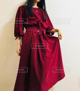 赤いワンピースを着てスカートの端をつまむ女性の写真・画像素材[869930]