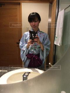 洗面台の前で自撮りをする水色の浴衣姿の女性の写真・画像素材[871365]