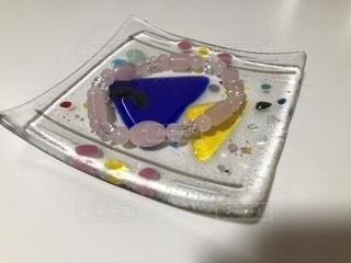 魚の模様のガラス小物入れにのったローズクォーツのブレスレットの写真・画像素材[877313]