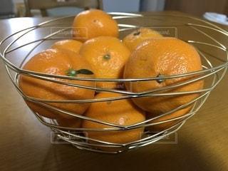 テーブルの上の果物カゴに盛られたみかんの写真・画像素材[920313]