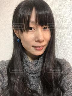 青いピアスをした女性の顔のアップの写真・画像素材[1012245]