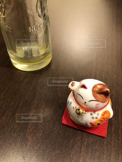 テーブルの上の招き猫と空き瓶の写真・画像素材[1025234]