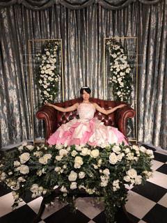 ピンクのフリルドレスを着てソファに腰掛ける女性の写真・画像素材[1639919]