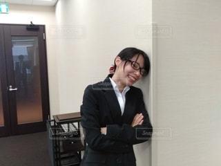 壁にもたれて腕を組み照れ笑いを浮かべる眼鏡をかけたスーツ姿の女性の写真・画像素材[2778211]