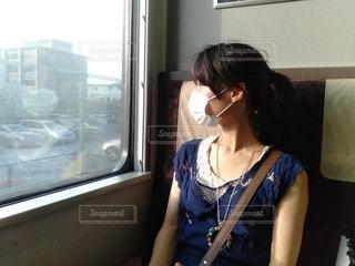 電車の座席に座って窓を眺めるマクスをした女性の写真・画像素材[3381140]
