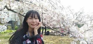 桜の木の下で笑顔を見せるロングヘアーの女性の写真・画像素材[3381141]