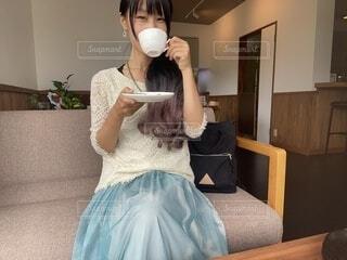 カフェのソファに座って飲み物を飲む女性2の写真・画像素材[4774598]