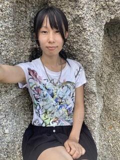 岩の窪みに収まって微笑む女性の自撮りの写真・画像素材[4774611]