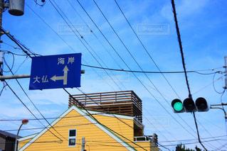 交通信号と道路標識建物の側面を離れて掛かるの写真・画像素材[868292]