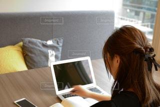 ラップトップコンピュータを使ってテーブルに座っている女性の写真・画像素材[2441030]